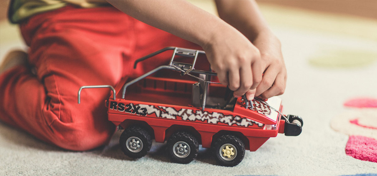 Photo of child playing with toy vehicle
