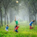 Photo of four children playing with a ball