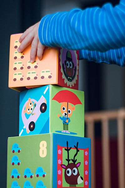 Photo of toddler stacking toy boxes